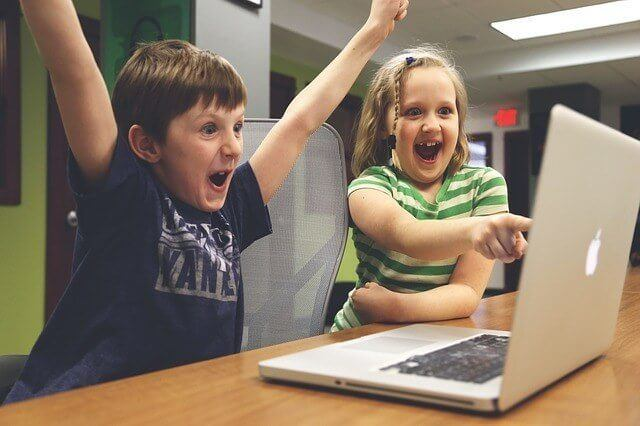 children cheering at computer